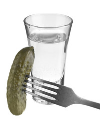 vodka in a glass and salted cucumber on a fork