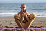 Handsome man stretching practicing yoga on coastline
