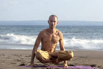 Spirituality man sits lotus pose yoga and rises up by hands