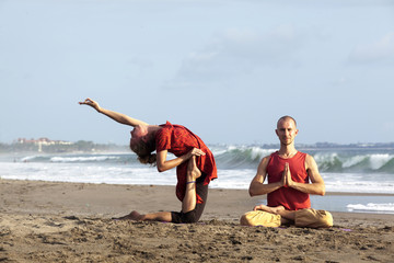 Woman doing exercise yoga with man sit in pose lotus near by