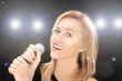 Beautiful blonde girl with microphone singing