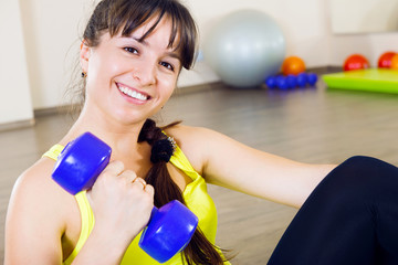 Young smiling woman exercising with dumbbells