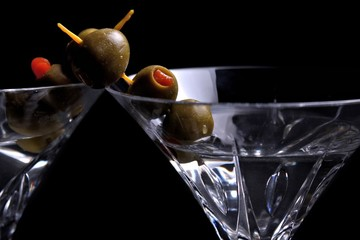 Two martinis on black with olives