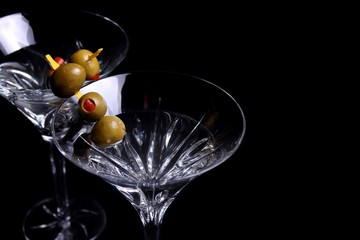 Two martini glasses with olives on black