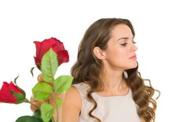 Displeased young woman taking flowers