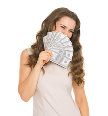 Portrait of happy young woman hiding behind fan of dollars