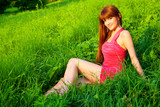 Young beautiful redhead woman sitting on grass