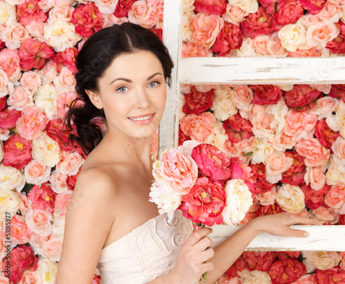 woman with old ladder and background full of roses