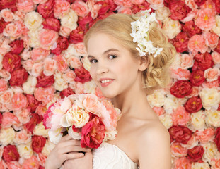 woman with bouquet and background full of roses