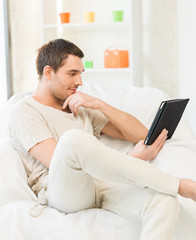 man sitting on the couch with tablet pc
