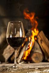 Copa de vino tinto con fuego de fondo.