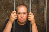 Young man behind the bars