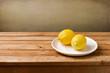 Fresh lemons on plate on wooden table