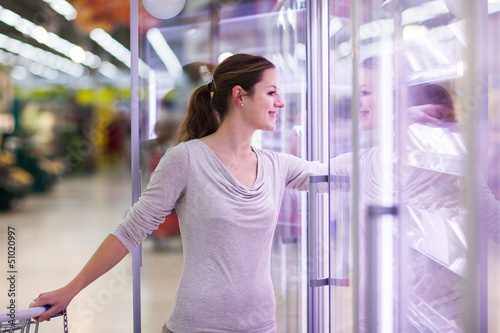 Young woman shopping for meat in a grocery store