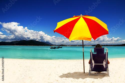 Woman with sun umbrella on the beach