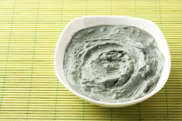 Cosmetic clay for spa treatments, on bamboo background