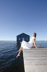 Peaceful woman white dress on boardwalk at sea