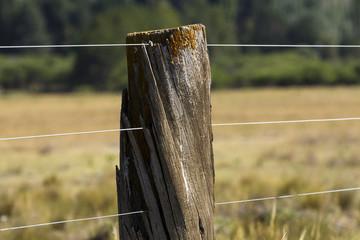 Poste de cerco alambrado en el campo.