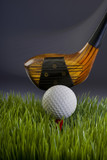 Golf ball and wood driver showing motion.
