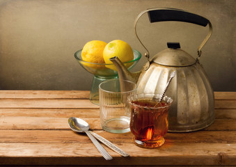 Vintage still life with teapot and lemons on wooden table