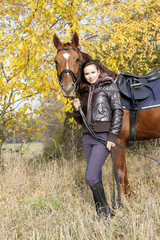 equestrian with her horse on autumnal meadow