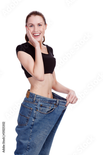 Surprised girl in big jeans. White background