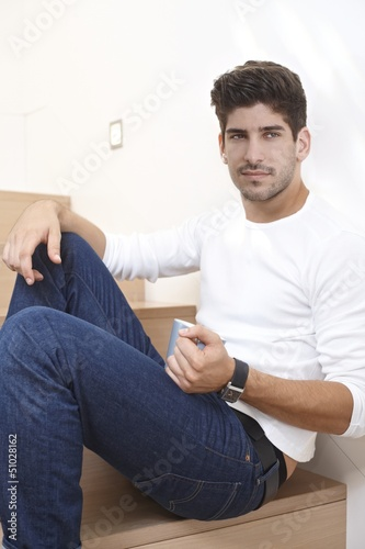 Daydreaming handsome man sitting on stairs
