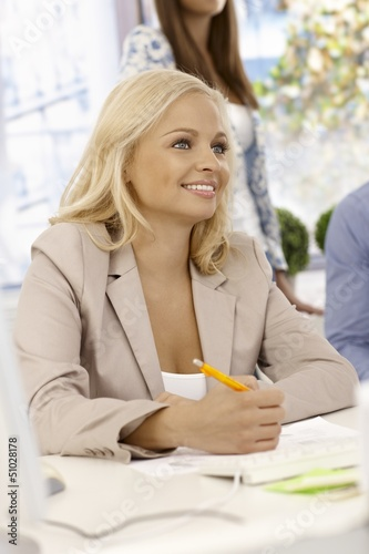 Portrait of attractive businesswoman writing