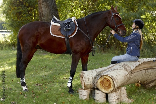 Horse and rider taking a break in the woods