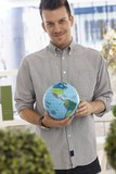Happy man holding small globe