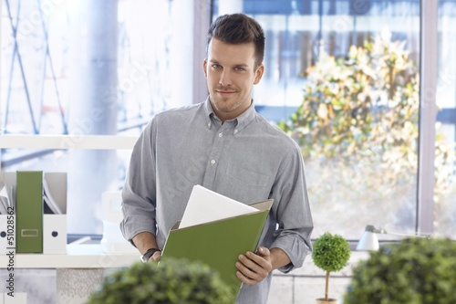 Portrait of casual office worker with folder