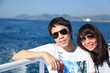 Happy asian couple on a sailing boat