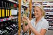 Frau beim Weinregal eines Supermarktes