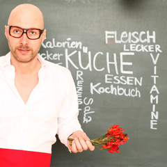 Mann mit Chili vor Tafel