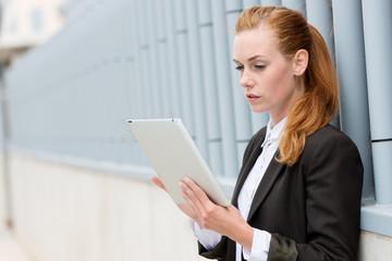 geschäftsfrau liest draußen am tablet-pc
