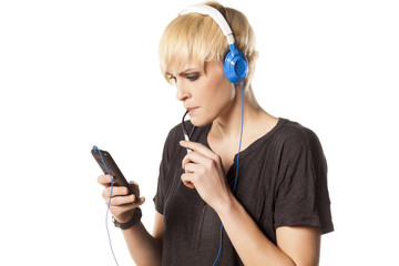 concentrated pretty blonde choosing a favorite song on her phone