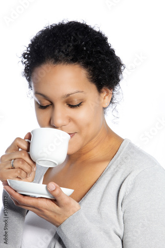 Dark skinned lady enjoys her coffee