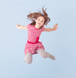 cheerful girl jumping on a blue background