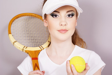 Young girl with tennis racket isolated on gray