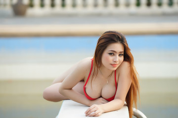 Beautiful young woman sitting by swimming pool