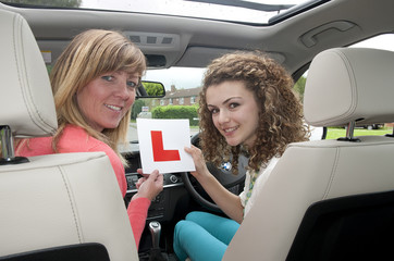Female driver holding L learner plate with instructor