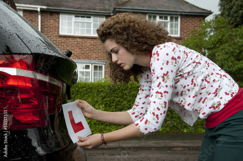 Young female driver attaching a L plate to car