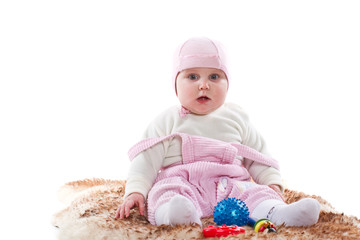 little girl sitting on a fur rug with toys