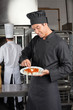 Chef Garnishing Dish In Kitchen