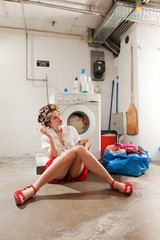 housewife in the laundry smokes and reads a book