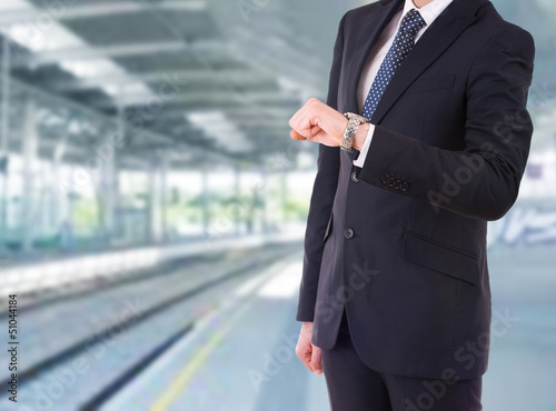 Businessman checking time on his wristwatch.