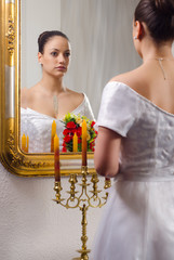 Beautiful bride in wedding dress looking at  the mirror