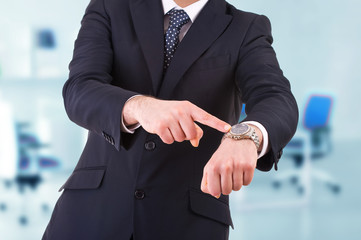 Businessman pointing at his wristwatch.