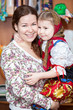 Happy mother holding small girl in Russian traditional clothes