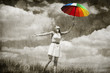 Beautifu girl with umbrella and suitcase at sky background.